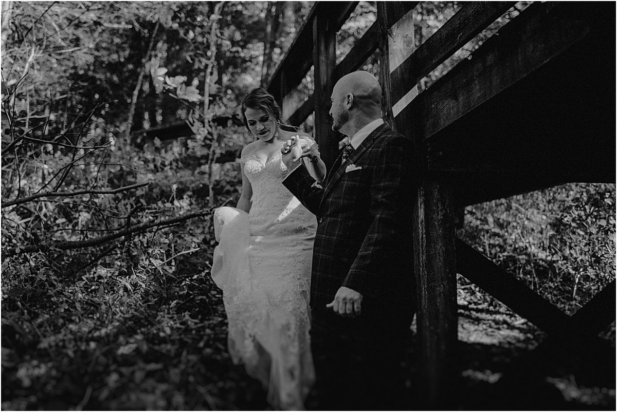 groom helping bride through forest in north carolina