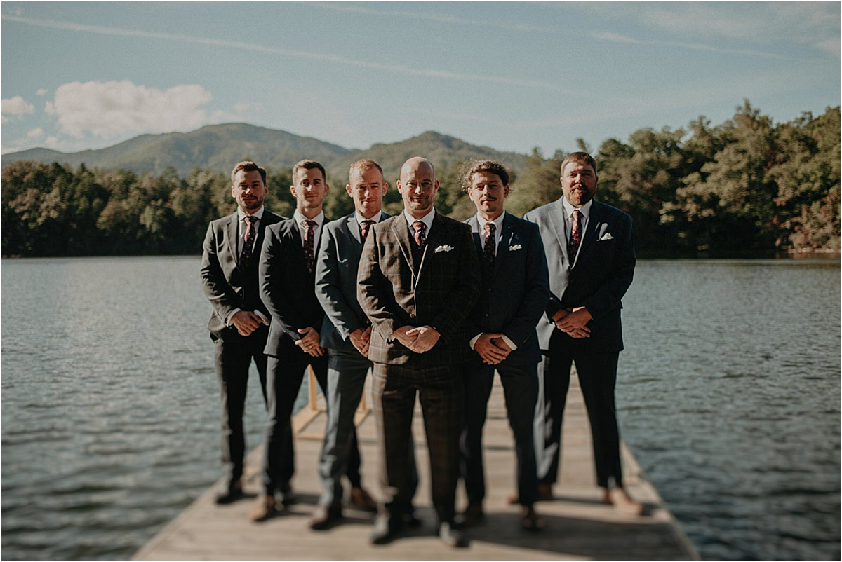 groomsmen posing together on lake dock