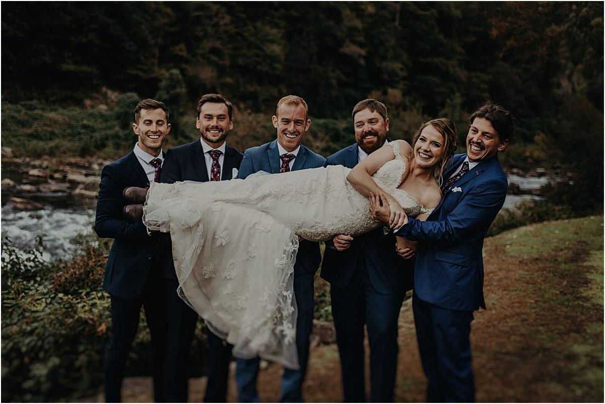groomsmen holding up bride after ceremony
