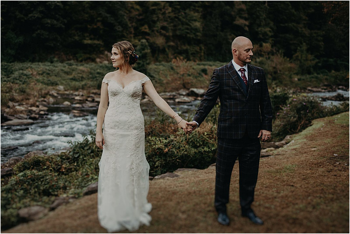 bride and groom holding hands in front of river