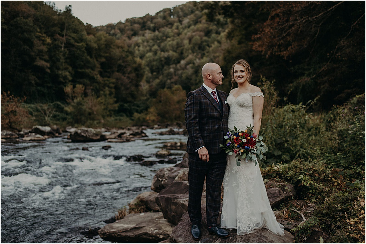 bride and groom in front of river in north carolina