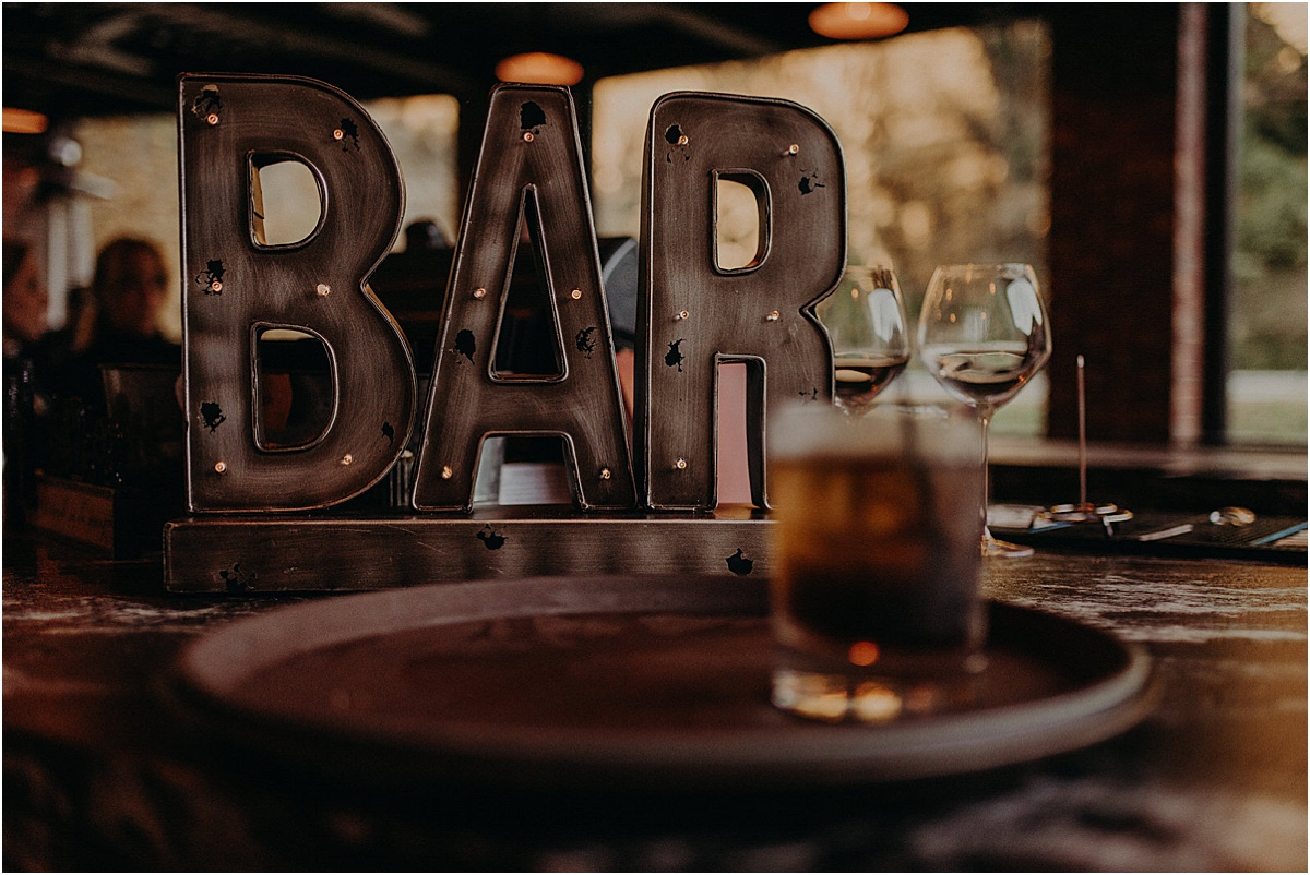 glass of whiskey in front of bar sign