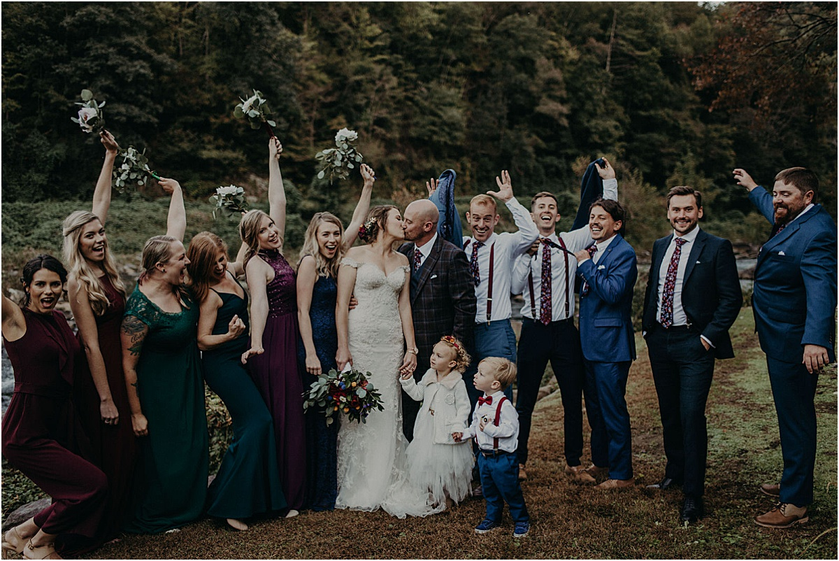 bridal party celebrating while bride and groom kiss