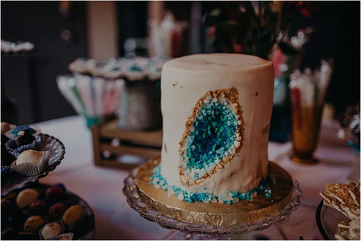white wedding cake with blue stones