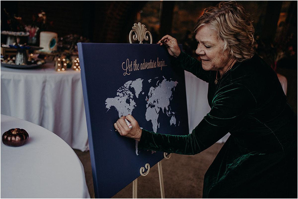 woman signing canvas at wedding reception