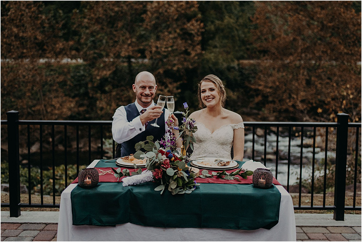 bride and groom toasting at dinner table