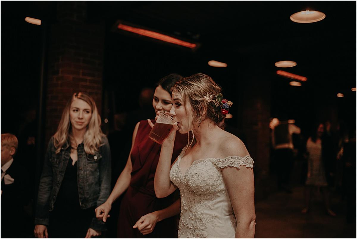 bride drinking beer during wedding reception