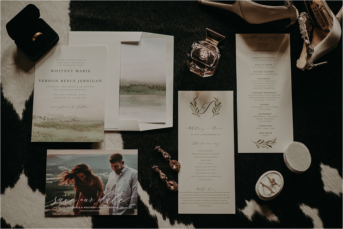 Wedding details and stationary laid out on a cow print rug in a Chattanooga, Tennessee Airbnb
