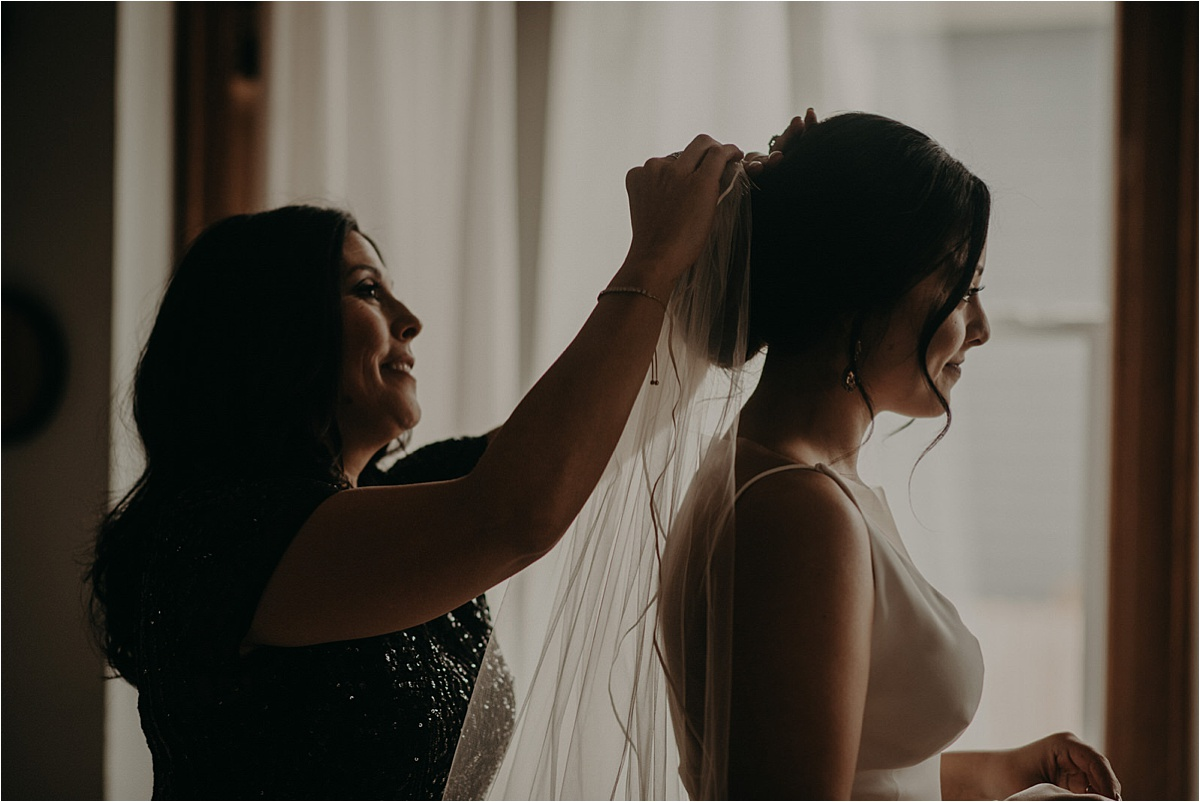 The mother of the bride positions her daughter's wedding veil