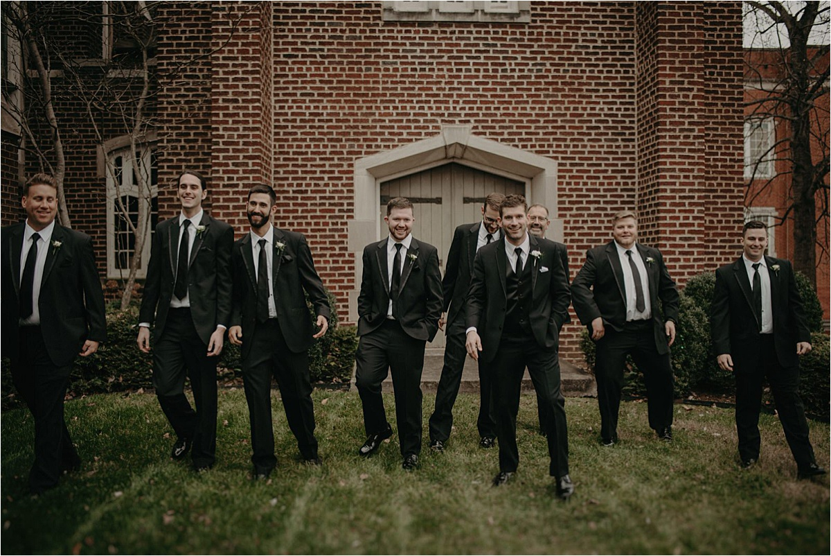 The groom and groomsmen dressed in black tie tuxes for this contemporary winter wedding