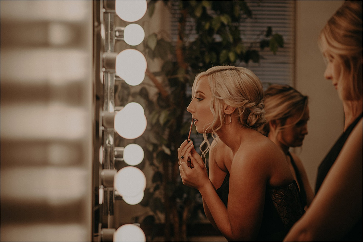 The bridesmaids touch up their makeup before the wedding ceremony