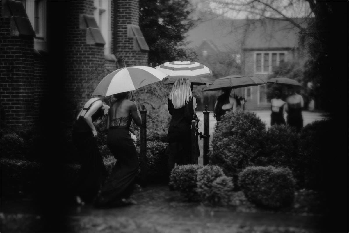 The wedding party heads to the ceremony under the cover of umbrellas at this rainy winter wedding