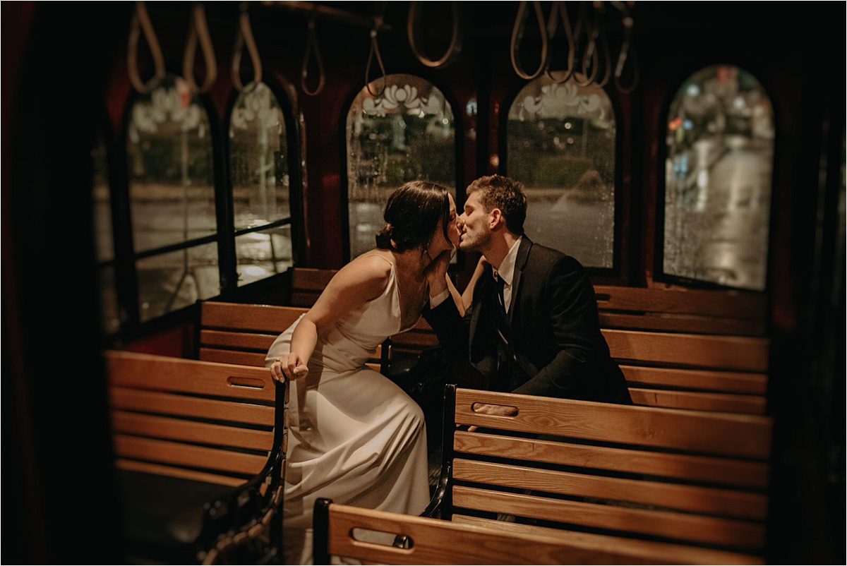 The bride and groom ride around in Chattanooga's trolley for late night rainy portraits after their wedding reception
