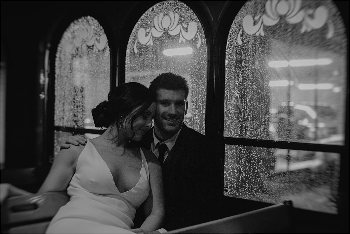Rain splatters the window of the trolley while the couple embraces