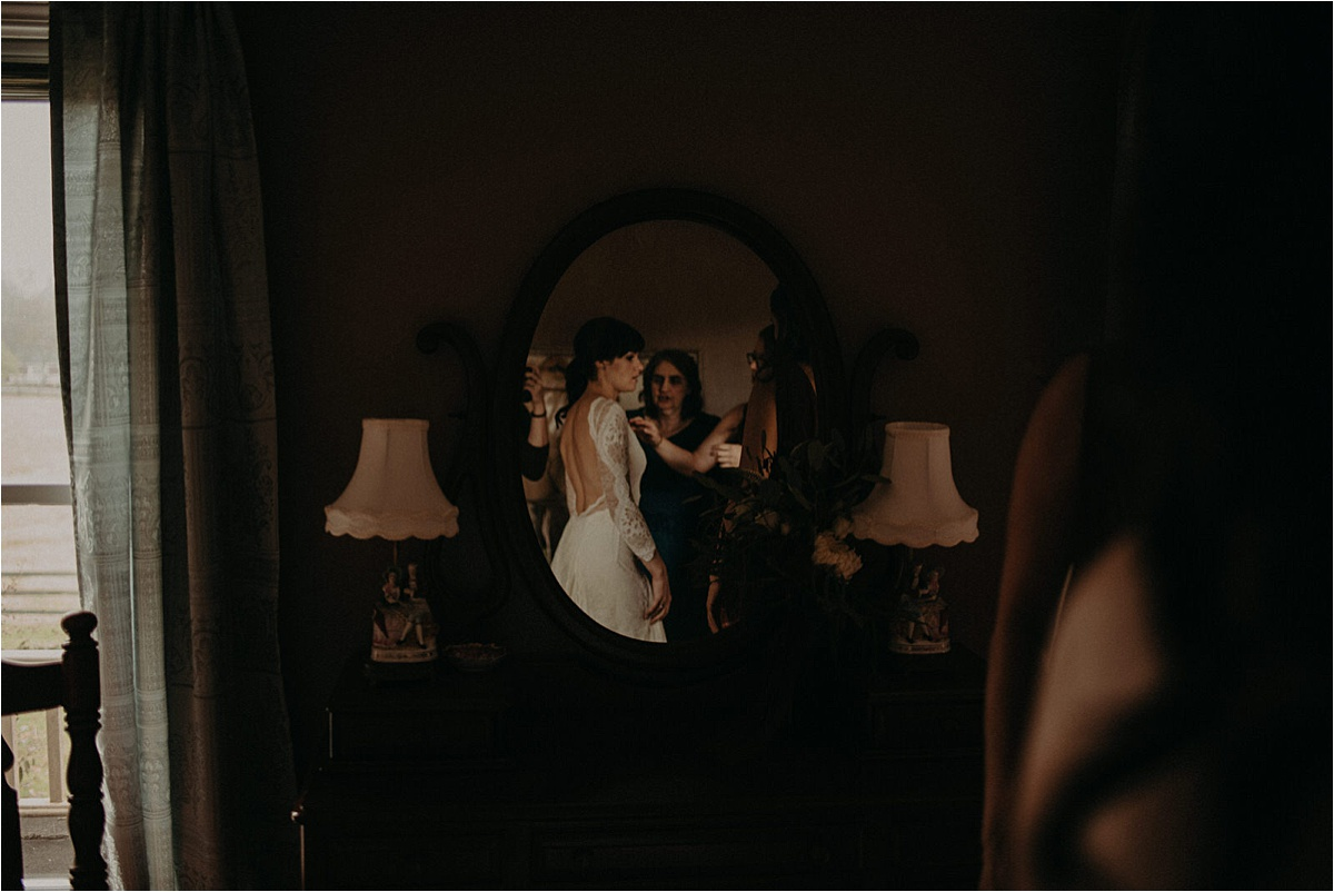 The bride's reflection in the mirror as her bridesmaids help fasten her gown