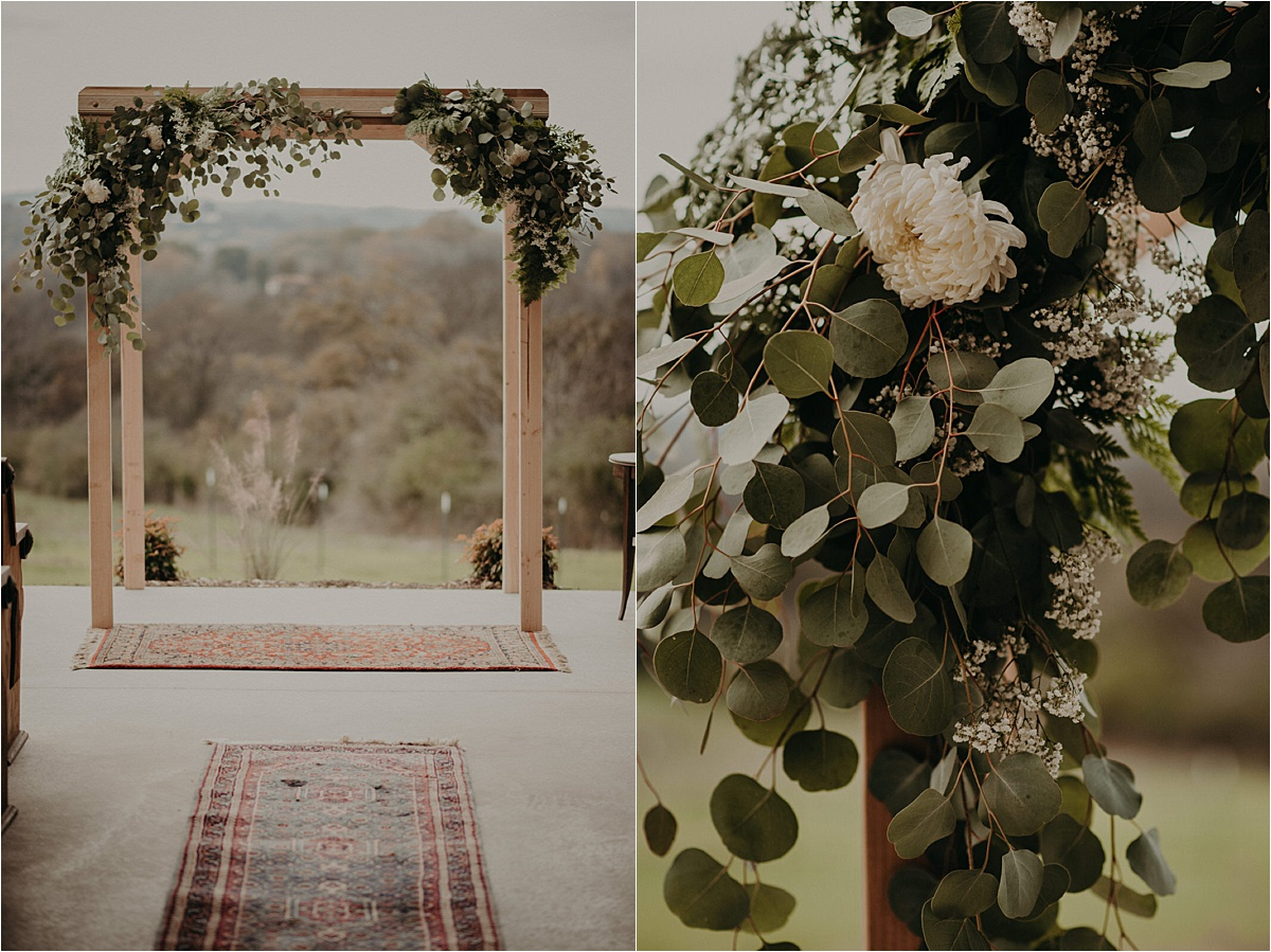 A rug runner leads to the ceremony altar decked with eucalyptus and greenery and white blooms at this Barn in the Bend wedding.