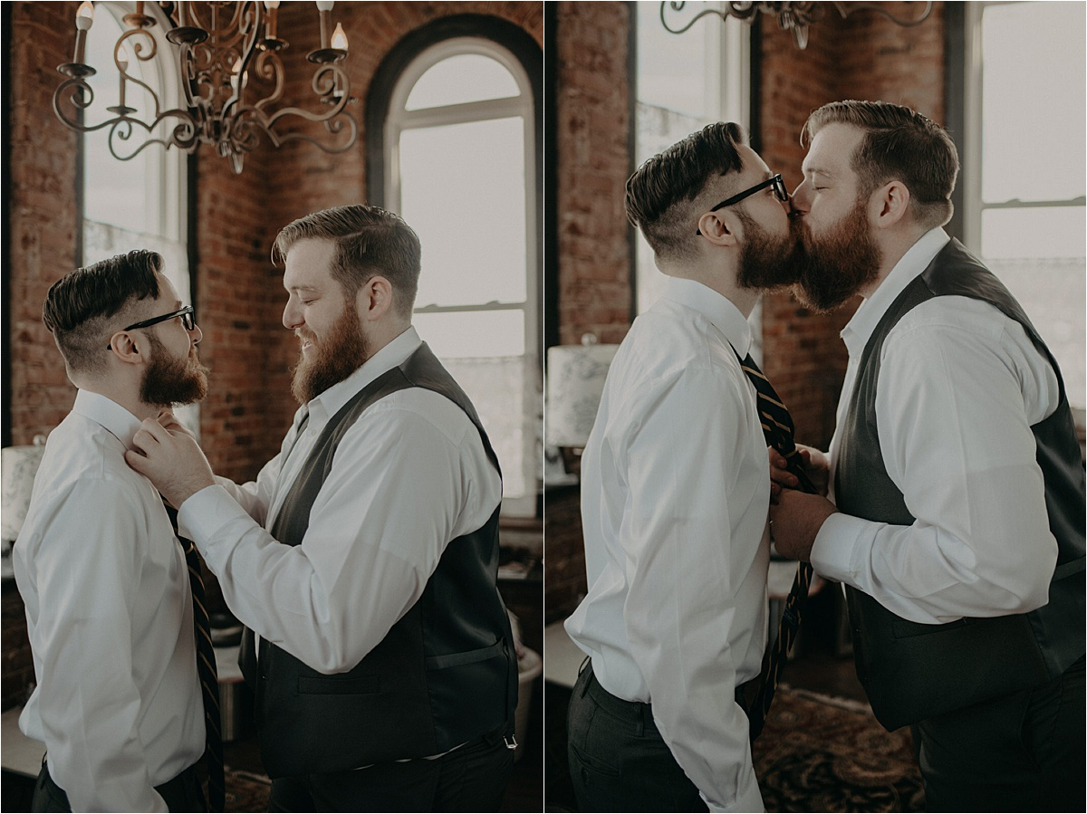 The grooms share a quick kiss as they help each other tie their neckties.