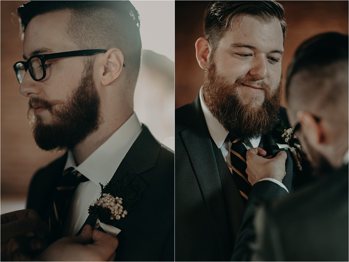 The groom pins his groom's boutonnière to his jacket lapel.