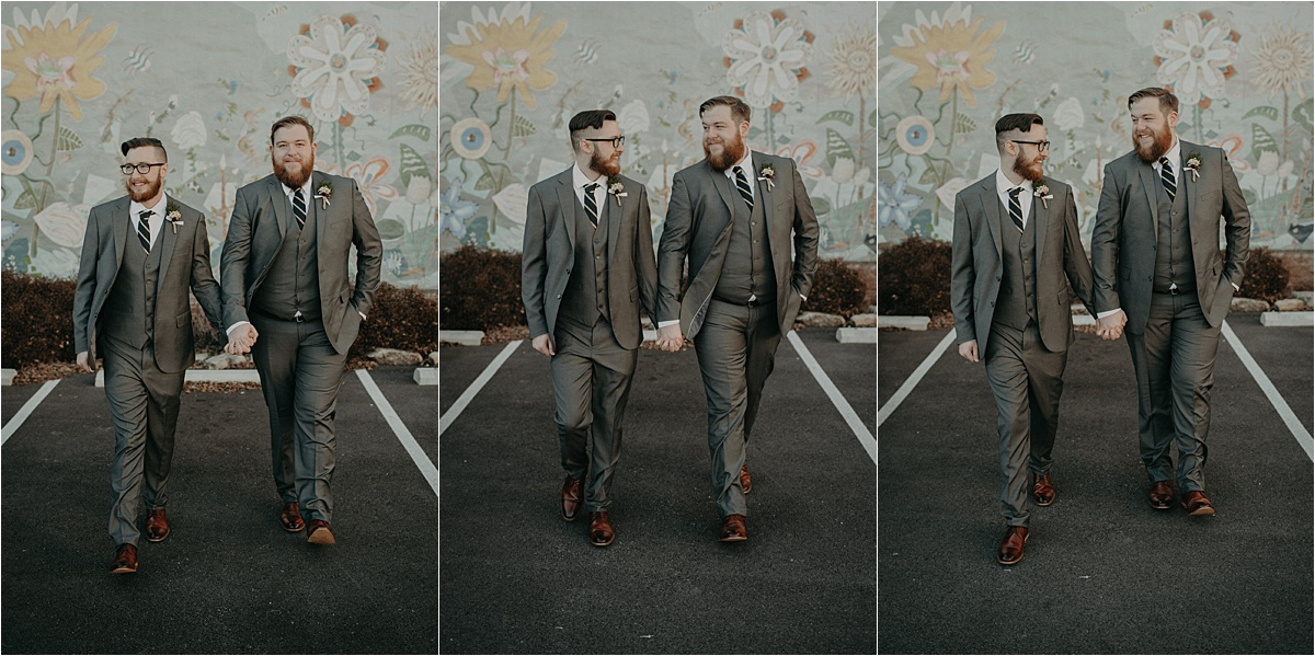The grooms walk hand in hand outside of a southside Chattanooga, Tennessee wall mural.