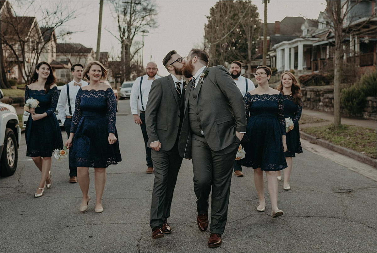 The grooms' wedding party walks down the neighborhood street together outside of the Church on Main.