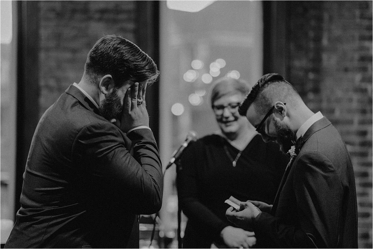 The groom wipes away tears as his groom reads his handwritten vows