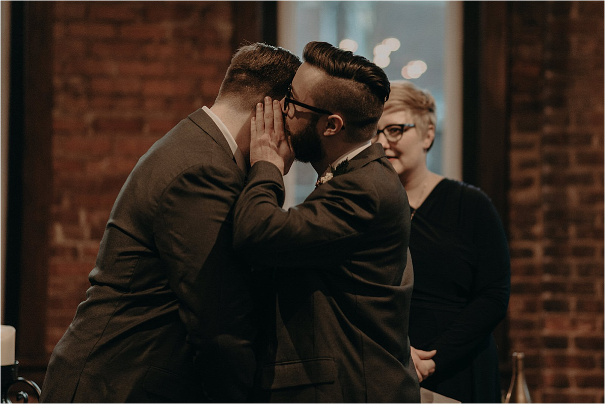 The groom whispers a secret vow into his soon-to-be-husband's ear