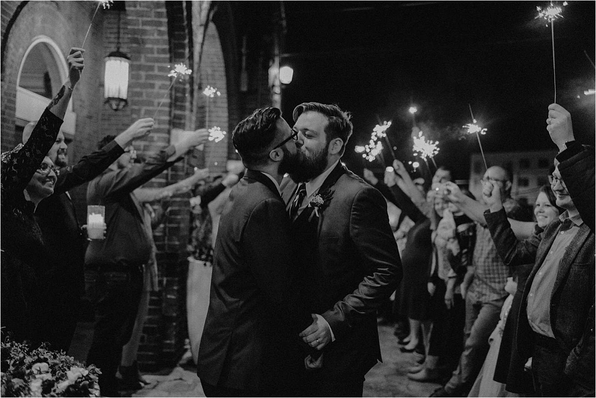 The grooms share a kiss at their sparkler grand exit outside of the Church on Main in Chattanooga, Tn's south side neighborhood