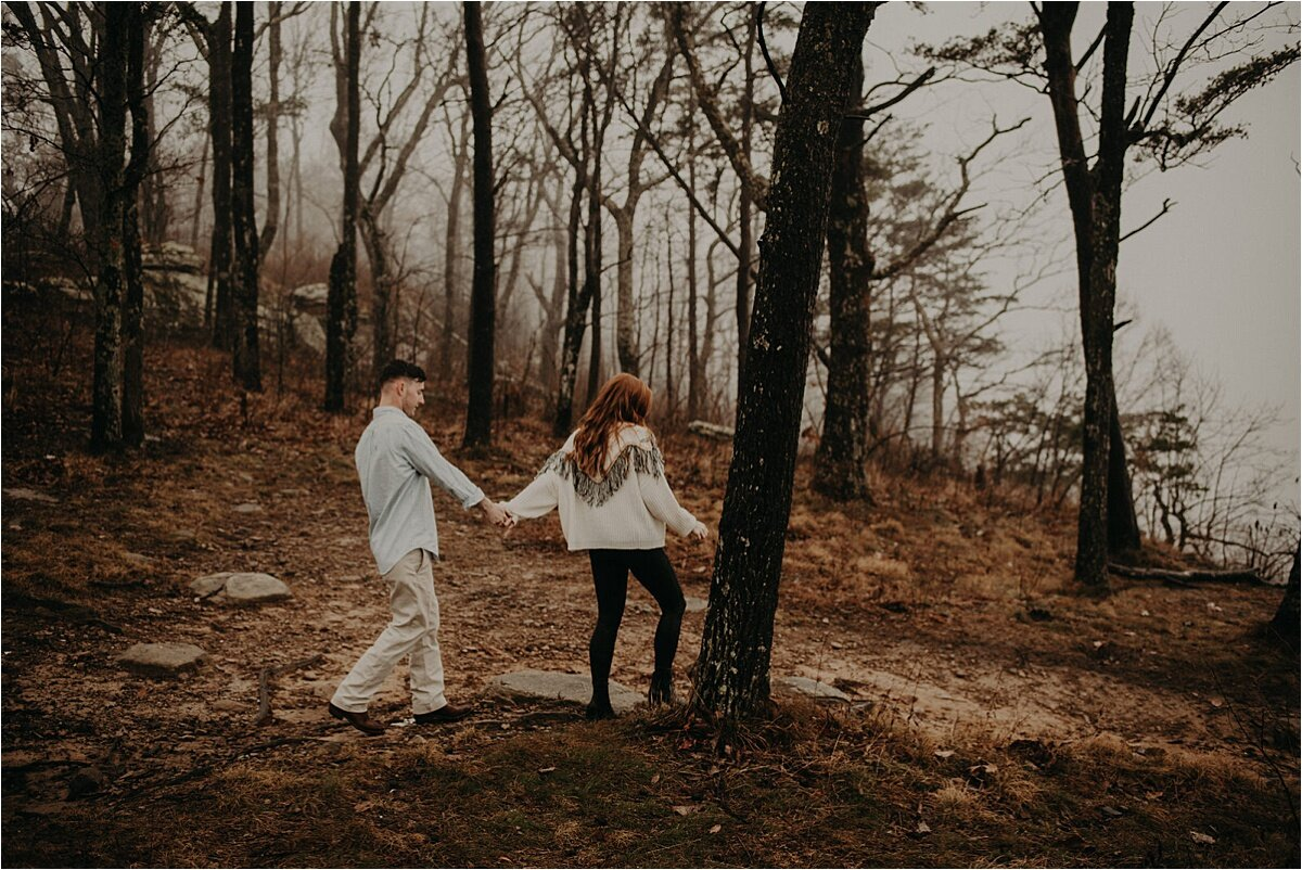 The engaged couple walks toward the foggy cliff on   Lookout Mountain, Tennessee