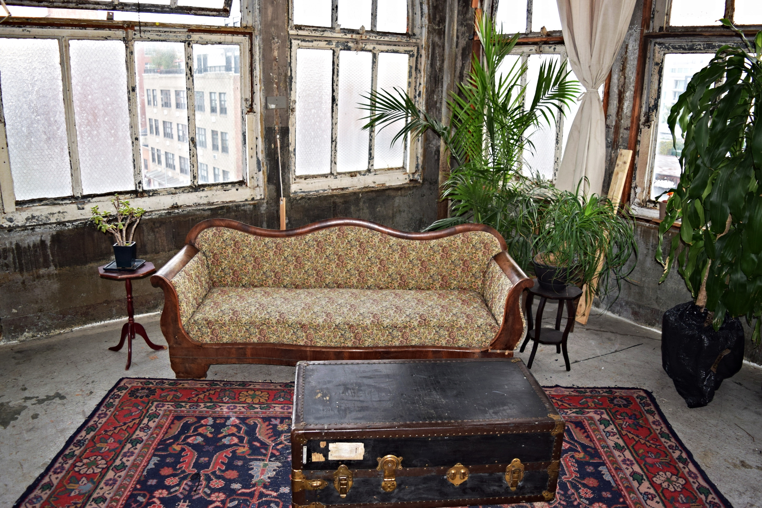 Vintage sofa, distressed Persian rug, steamer trunk, side tables and plants