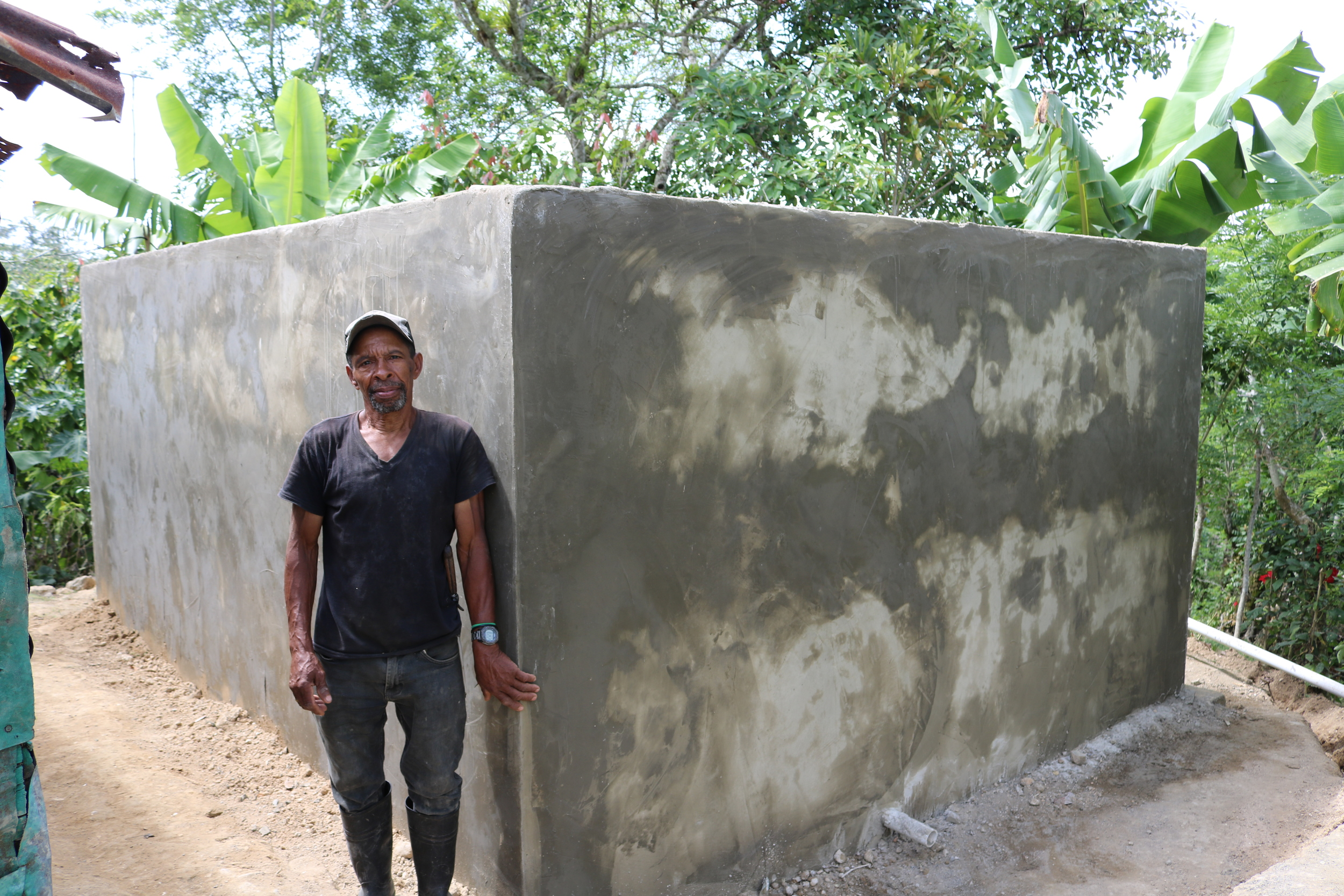 The tank now sits in the same spot where Jose's kitchen used to be. Here he is posing next to the tank. Although you can't see it in his face, he was so overjoyed by the fact that the tank was situated right next to his house.