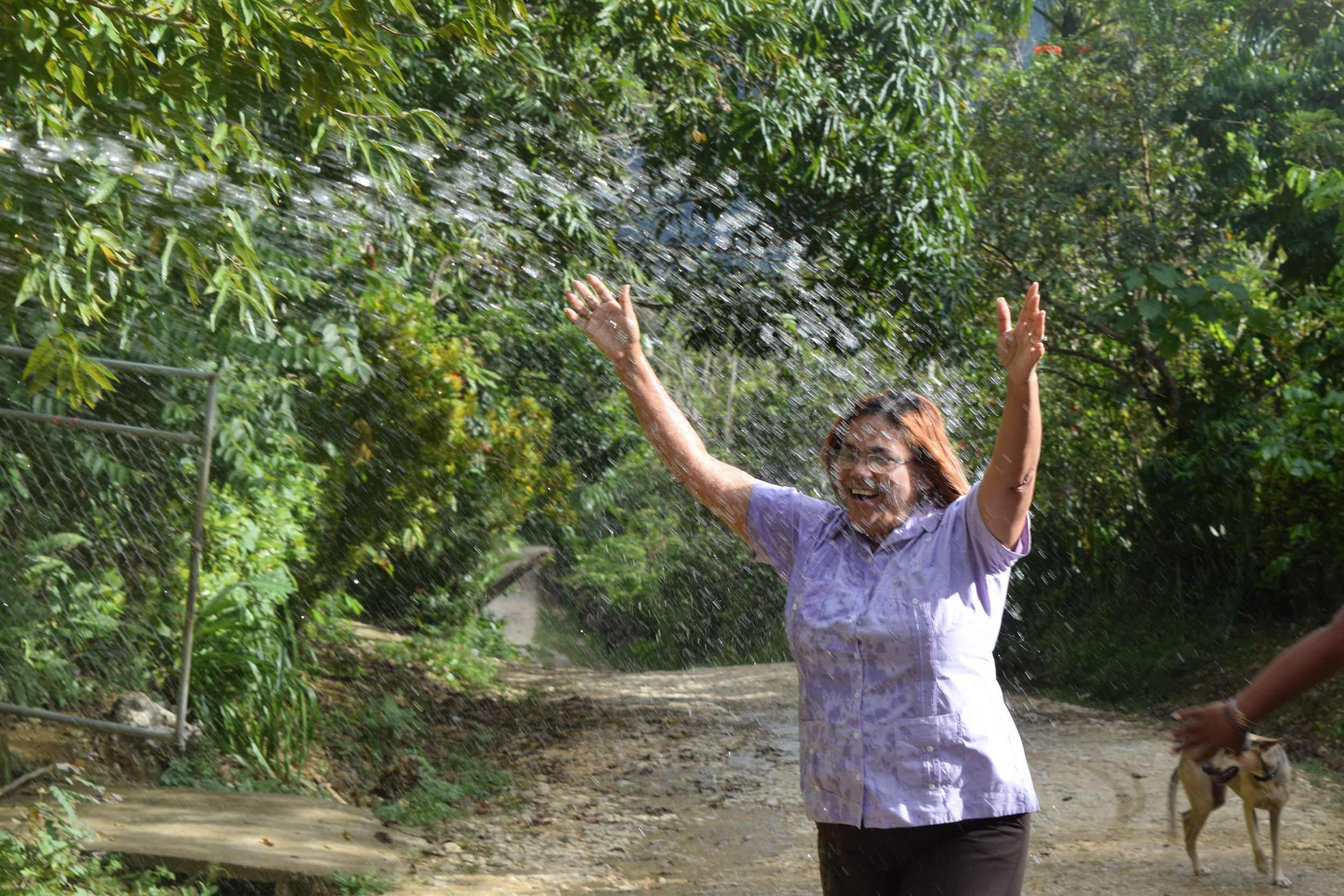 Senora Estrella, Vice-President of the Water Committee, celebrates as water arrives to the town.