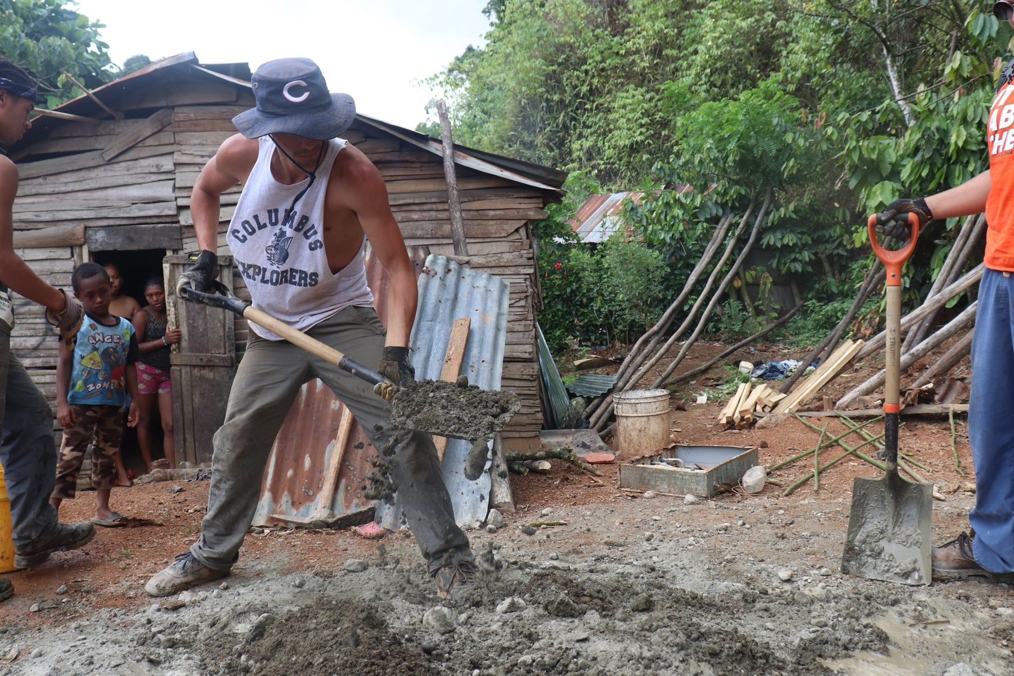 Volunteer digging a hole for an improved pit latrine.jpg