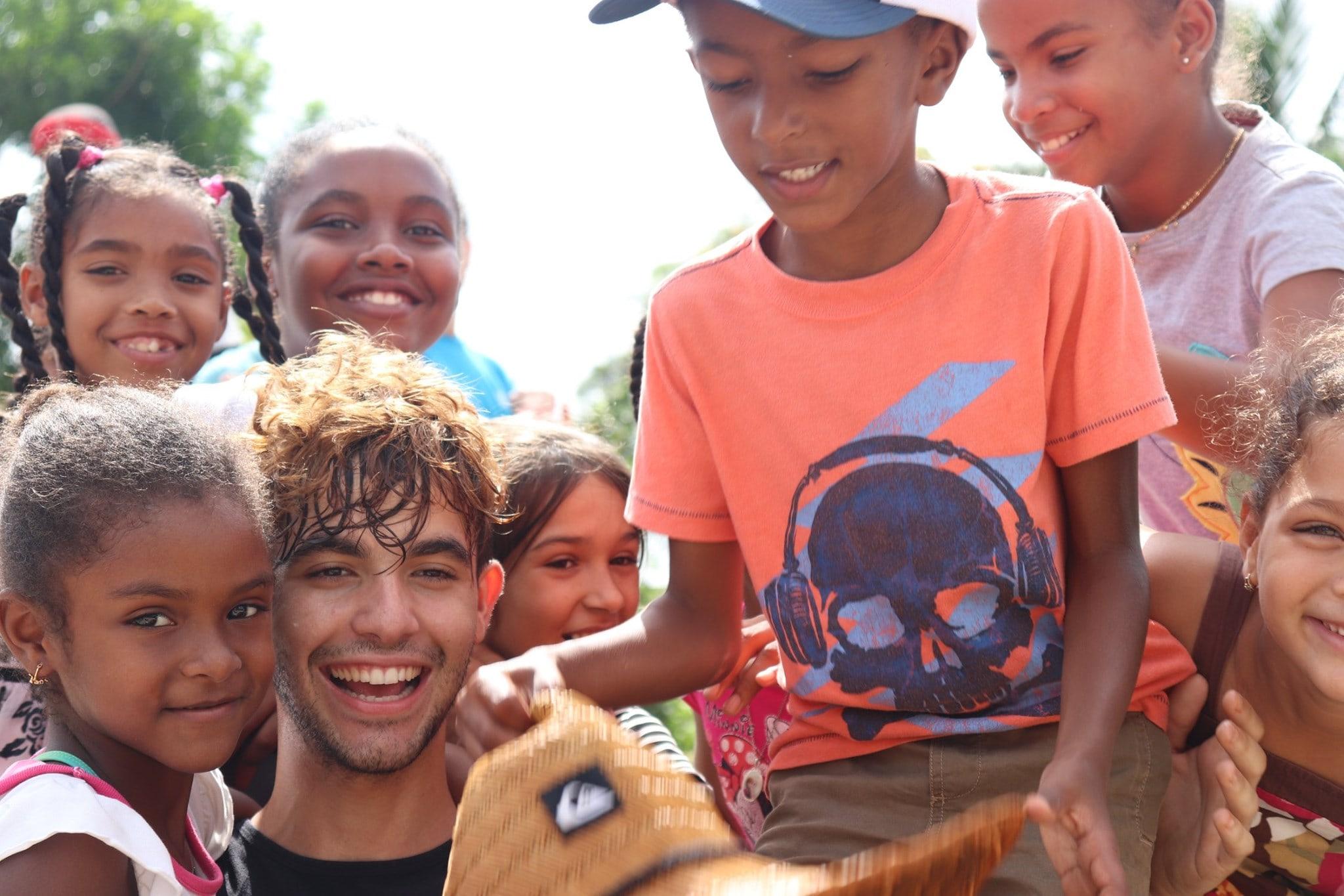 International Volunteer sorrounded by community kids.jpg