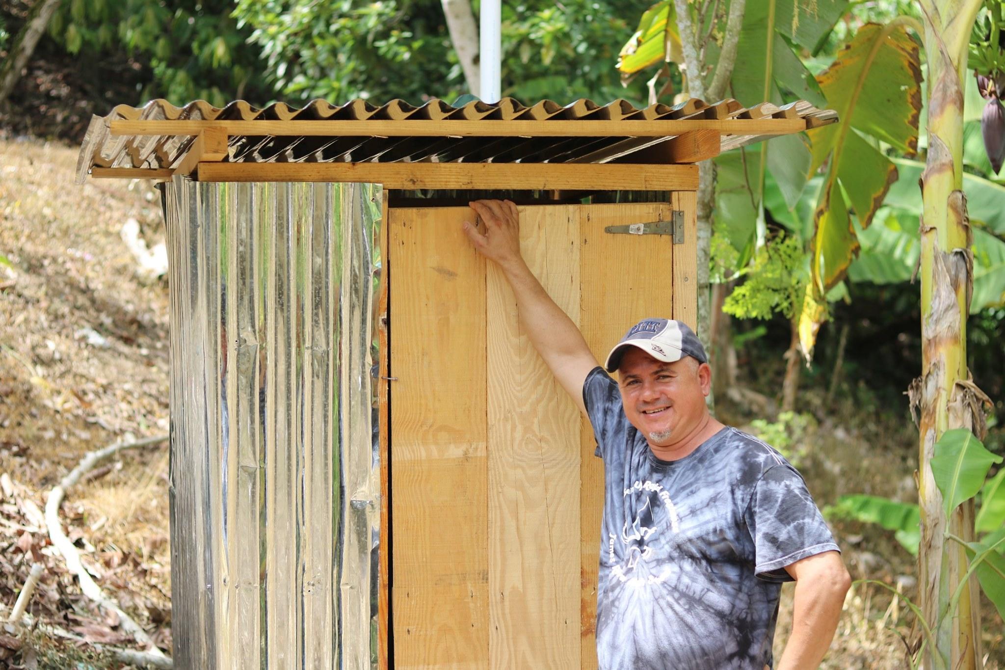 blue-missions-volunteer-posing-next-to-latrine.jpg