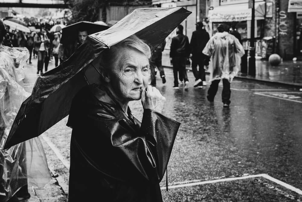 A photograph of an old lady with an umbrella taken on Portobella Road during the Notting Hill Carnival in London