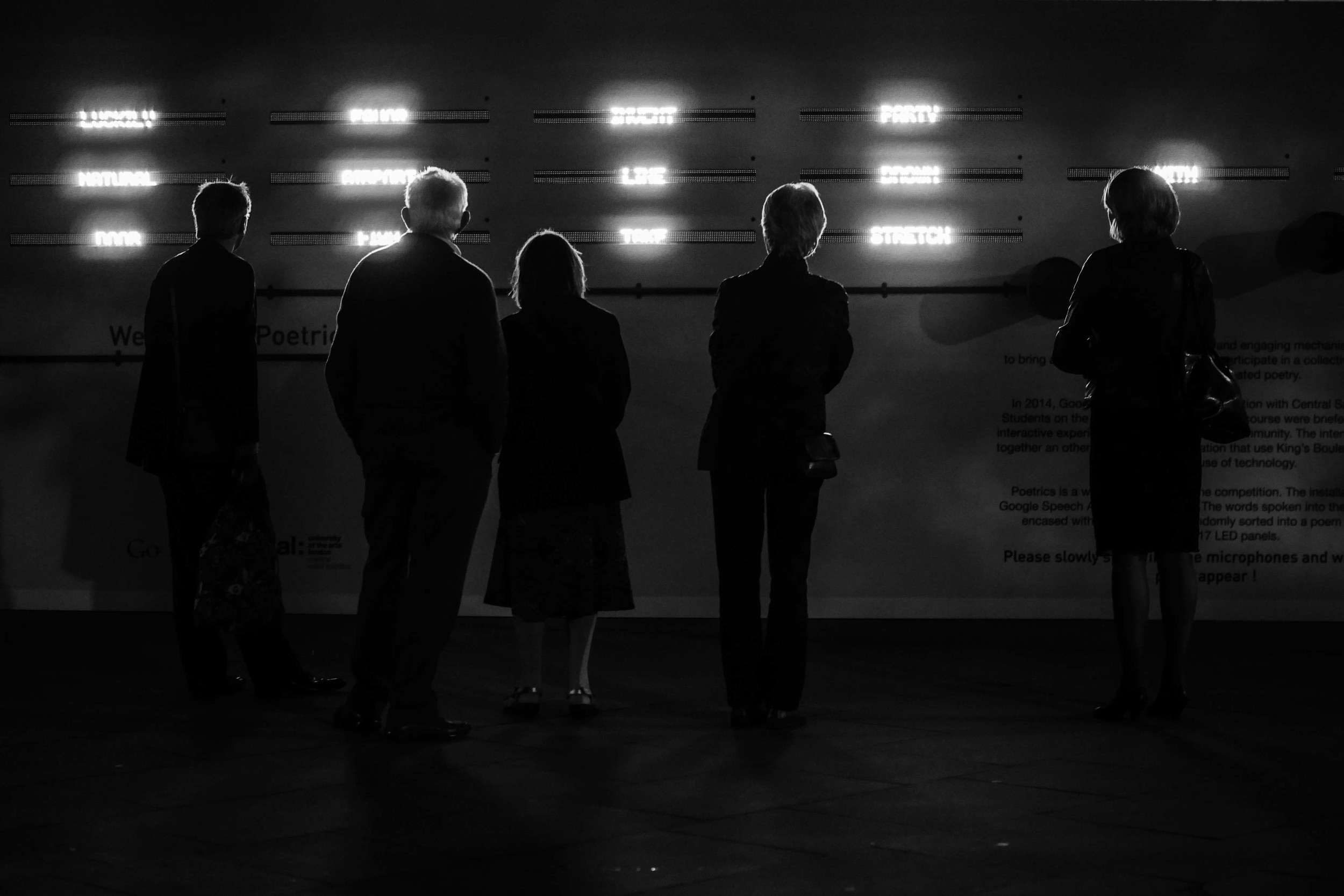 A photograph of a group of people interacting with the Poetrics installation outside King's Cross Station in London
