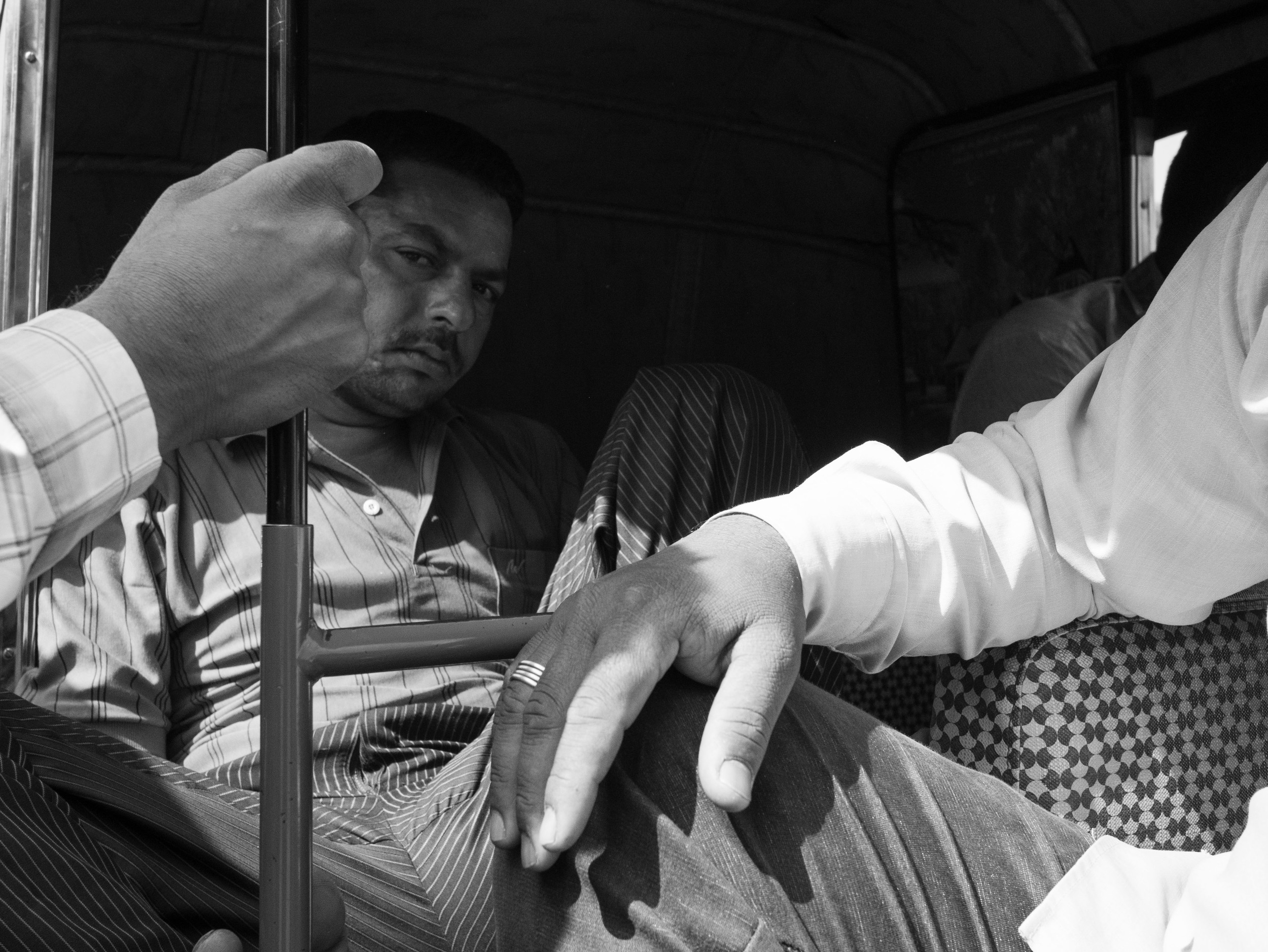 A candid photograph of an autorickshaw driver taken by street photographer Gagan Sadana in Vadodara, Gujarat in India as part of the street photography series 'For Hire'