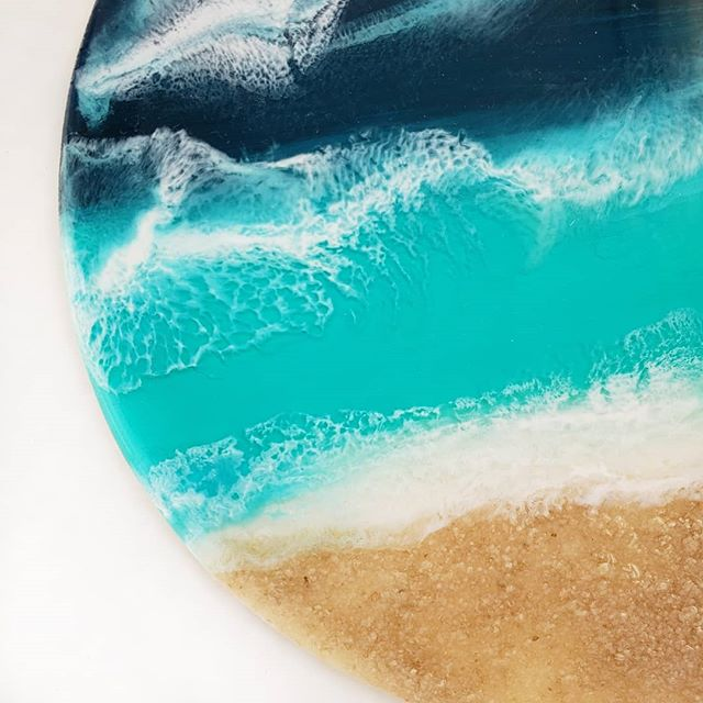 """Still catching up with #aprilforartists with """"closeup"""" day.  I've been working really small to start with resin since it's pretty pricey.  Most of my resin pieces are literally less than 3"""" so far, haha! This piece is 6"""" diameter though.  It has real sand and just 2 layers.  It's not done which kinda coincides with """"work in progress"""" day coming up soon.  I'm anxious to snag some more resin to keep playing with these beaches!  Swipe to see a closeup of one my acrylic ribbon pours that I'm still mesmerized by too. #fluidartwork #fluidart_daily #fluidart #acrylicpour #resin #resinwaves #lacing #resinartwork #resinart #beachart #oceancolors #beach #ocean #modernmaker #moderncrafts #wip"""