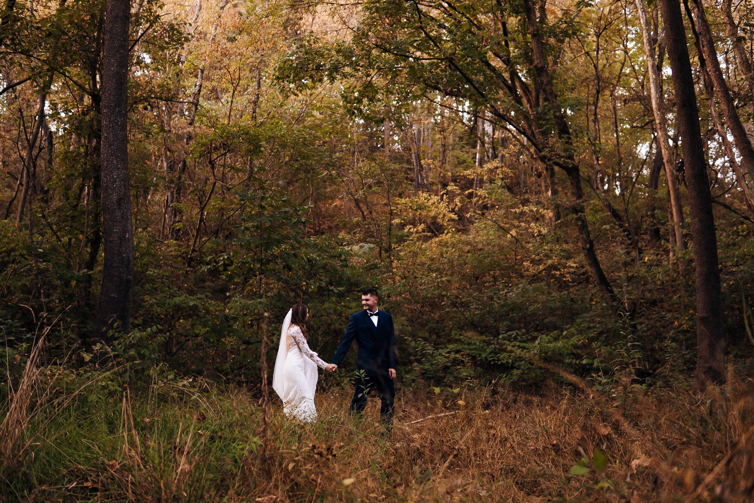 Bride and Groom walking in woods at wedding in Virginia