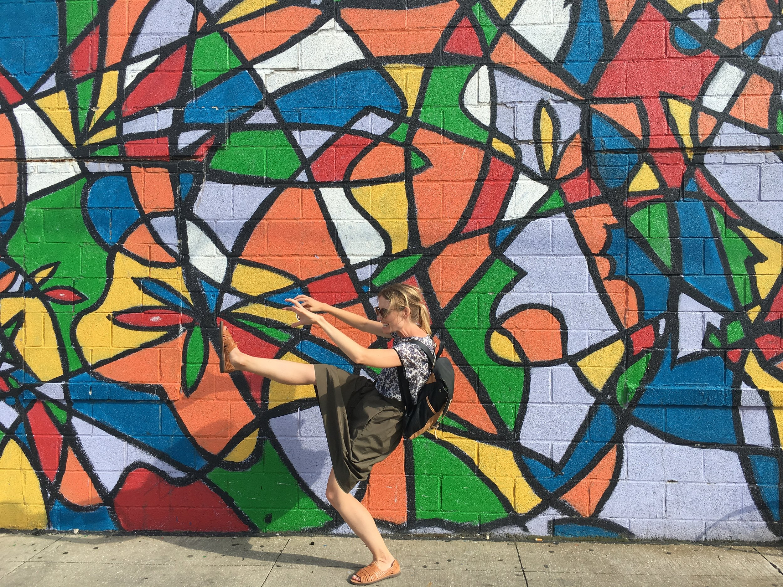 Mel = attacking the day in front of a mural in Ohio City.