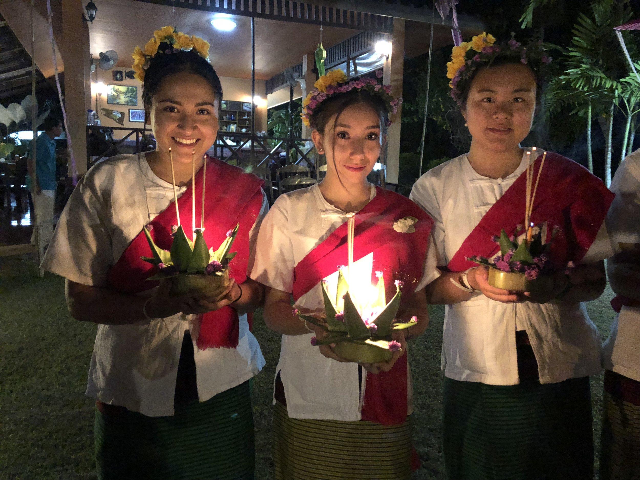 Cynthia, Ana, and Lena holding Loi Kratong lantern boats at the village farewell gathering.