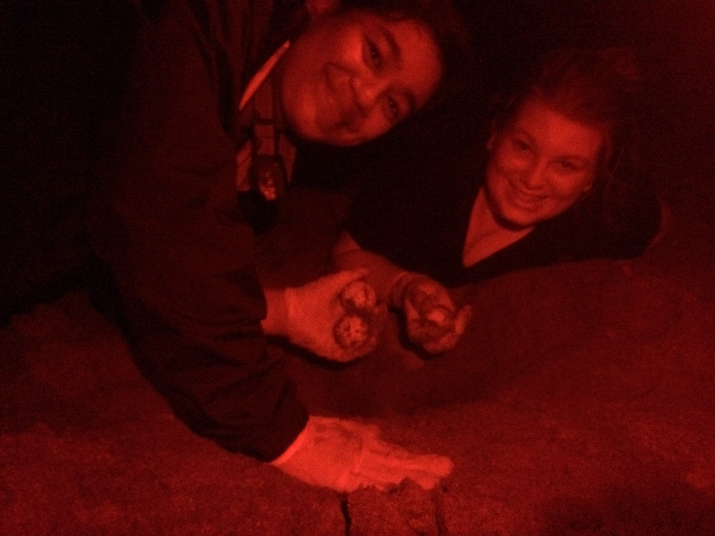 Hillary and April help in relocating green sea turtle eggs into a hidden nest with Kuemar Guanacaste turtle conservation project. (Photo taken with red light to not disturb turtles.)