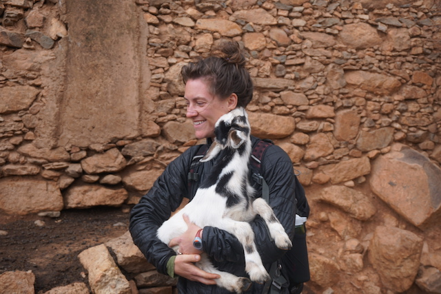 Kate and a goat having a moment of endearment after having tea with a family in a village.