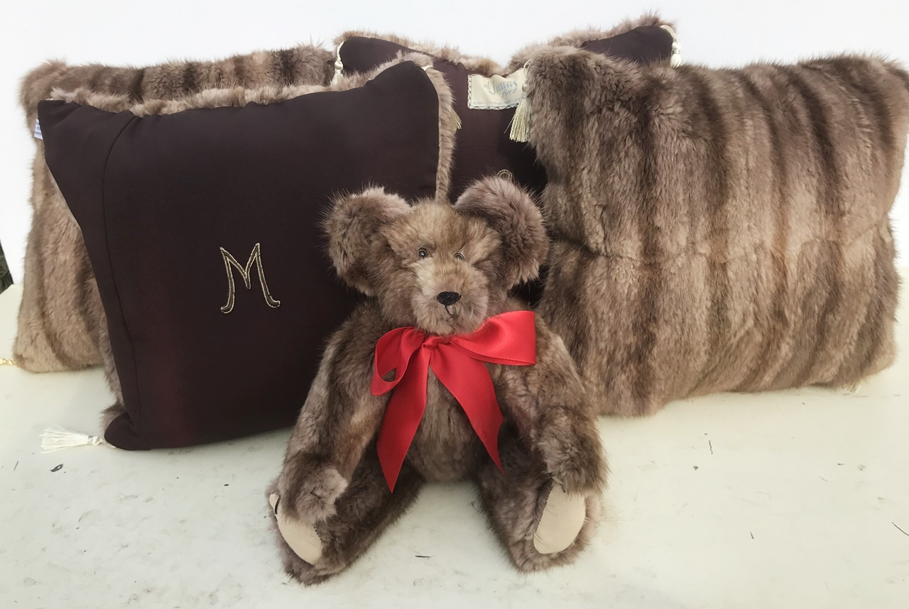 "Marylou sent us her kneelength vintage fur coat. We made a wonderfull, at least we think it is wonderful, 12"" bear. Then Vicky got 5 15x15 pieces from what was left. So, what we also made for her is one 15x15 pillow that is fur on both sides. Then the other three are fur as one side and the coat lining as the other. And on she sewed a mongram letter on each of the those. One of them also has the original coat label as well. she also added some small tassels as an extra touch. We think they're really cool."