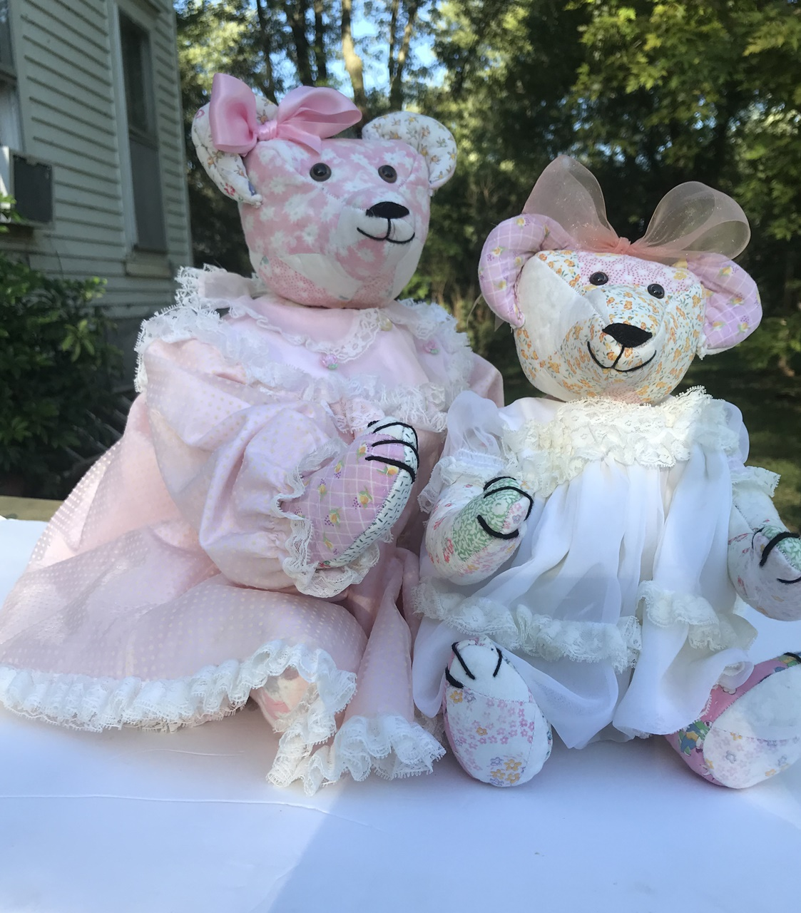We made these two bear s from a vintage quilt. Thiier little dresses are family pieces.