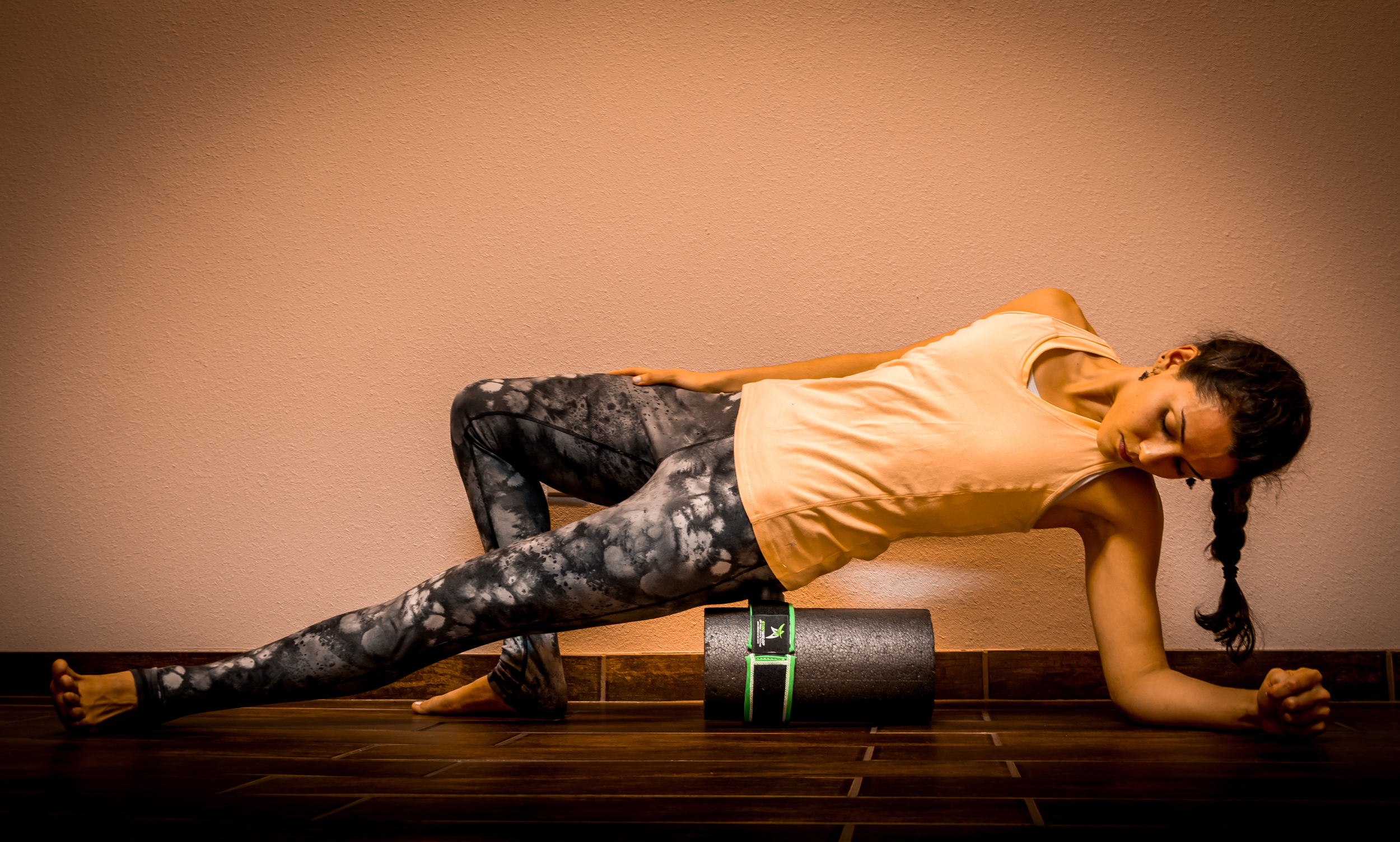 """Using the STARwrap with a foam roller to activate deep tissue that a foam roller just can reach on its own. Each STARwrap Performance Kit includes a 12"""" half foam roller to take with you on the go."""