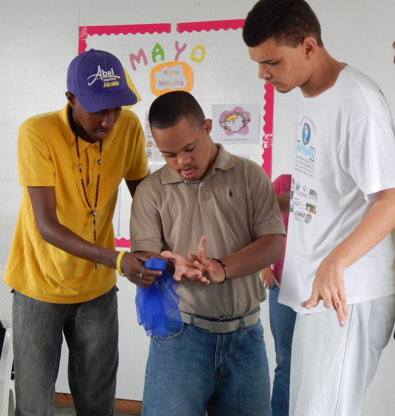 Cesar and Estarlin help their classmate with a game that develops their motor skills.