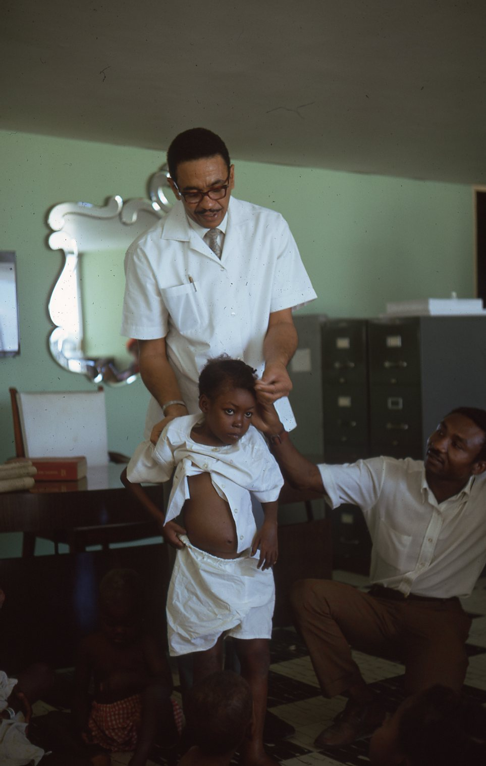Napo assists Dr Lionel Theard with a patient at Grace.