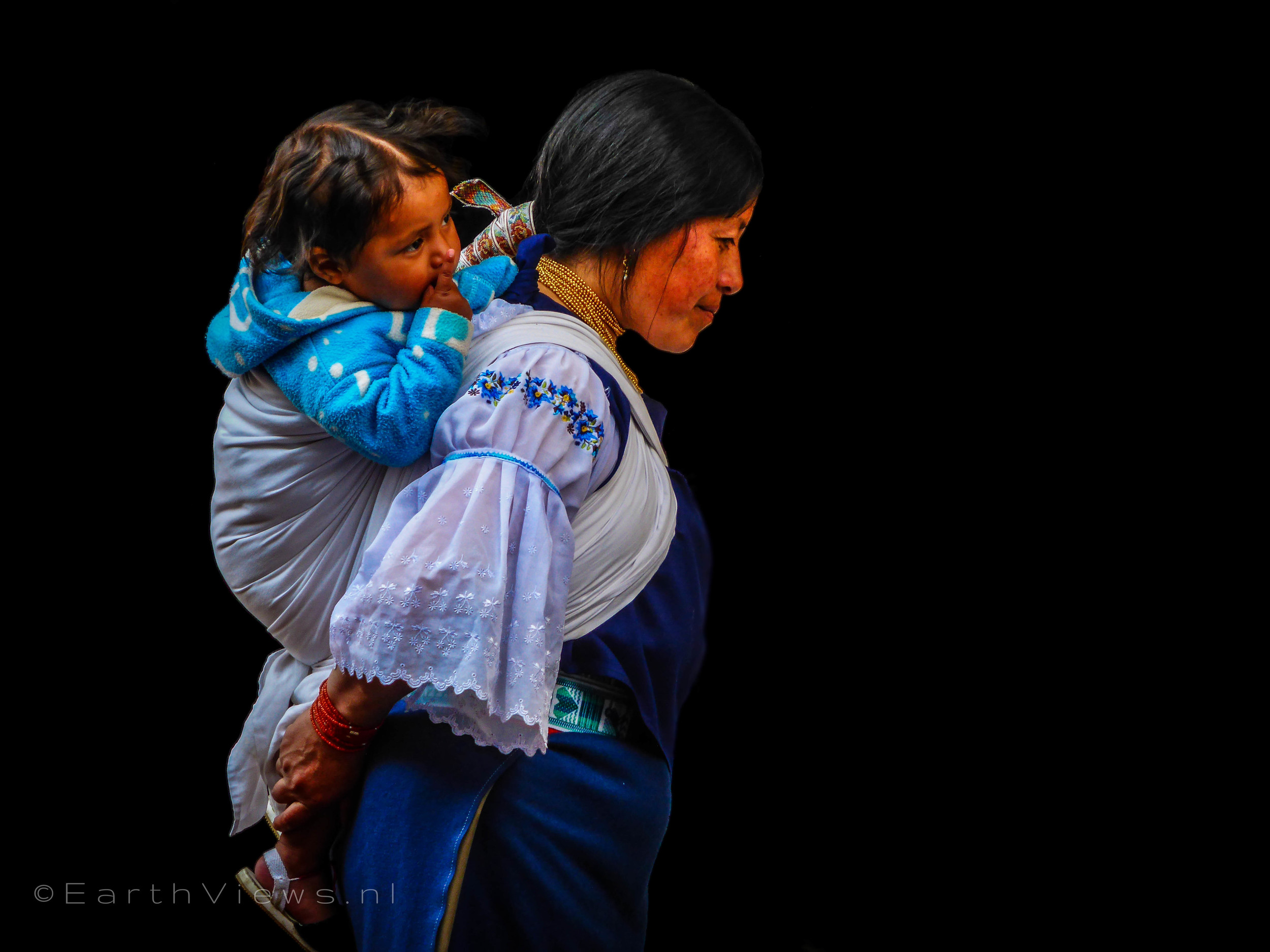 An Otavaleña in traditional style with her child on the Otavalo market.