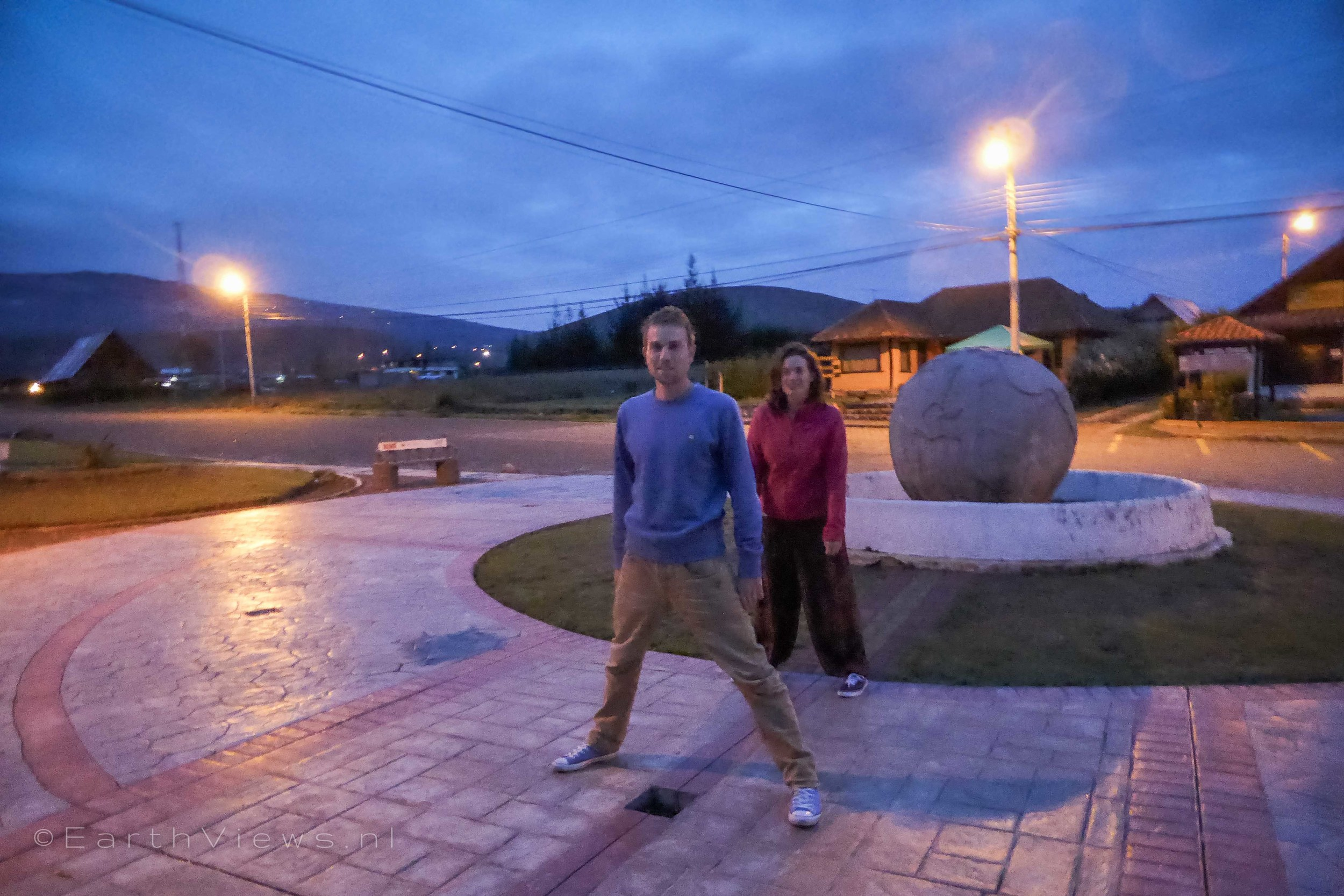 At the Equator: one leg in the Northern Hemisphere and one in the Southern Hemisphere.